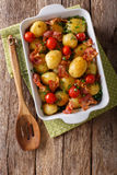 Baked new potatoes with bacon and tomatoes close-up in a baking Stock Photography