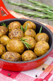 Baked new potatoes with curry and rosemary in a skillet, closeup. Baked new potatoes with curry and rosemary in a skillet, close-up vertical Royalty Free Stock Image