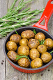 Baked new potatoes with rosemary in frying pan vertical Stock Image