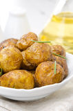 Baked new potatoes with spices and rosemary in a bowl, vertical Stock Images