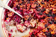 Baked oatmeal with berries and nuts, spoon in it, close-up Royalty Free Stock Photography