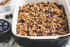 Baked oatmeal with blueberries and honey in oven dish. Oatmeal fruit crumble pie