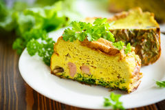 Baked omelette with sausages and greens Royalty Free Stock Image