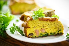 Baked omelette with sausages and greens Stock Photos