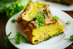 Baked omelette with sausages and greens Stock Photo