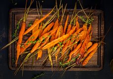 Baked organic carrots with thyme, honey and lemon. Organic vegan food. Top view royalty free stock image