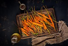 Baked organic carrots with thyme, honey and lemon. Organic vegan food. Top view stock image