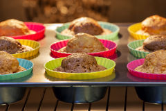 Baked in the oven muffins. Cakes in molds on a tray after baking in the oven Stock Image