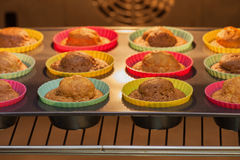 Baked in the oven muffins. Cakes in molds on a tray after baking in the oven Stock Photos