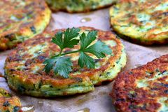 Baked in oven zucchini fritters, close-up. Delicious baked in oven zucchini fritters on baking paper, healthy and easy recipe, view from above, close-up Stock Image