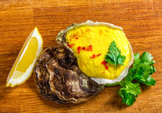 Baked oyster shell with cheese, served greens and lemon Stock Images