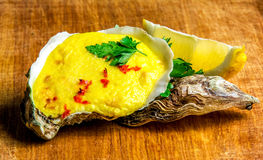 Baked oyster shell with cheese, served greens and lemon Stock Photo