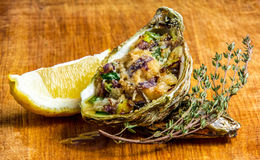 Baked oyster shell with cheese, served greens and lemon Stock Photography