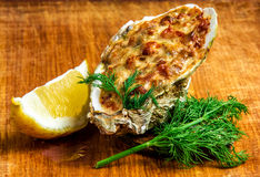 Baked oyster shell with cheese, served parsley and lemon Royalty Free Stock Photo