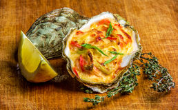 Baked oyster shell with cheese, served parsley and lemon Stock Image