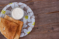 Baked pancakes on a plate with sour cream Stock Image