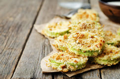 Baked parmesan zucchini crisps. On a dark wood background. the toning. selective focus royalty free stock image
