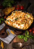 Baked pasta with broccoli, cauliflower, cheese and bechamel sauce. In a frying pan on wooden bachfround stock photography