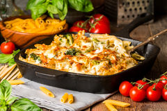 Baked pasta with broccoli, cauliflower, cheese and bechamel sauce. In a frying pan on wooden bachfround royalty free stock photo