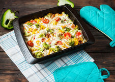 Baked pasta with broccoli and cheesy tomato sauce on wood background Royalty Free Stock Image
