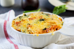 Baked pasta with spinach in tomato sauce Stock Photography