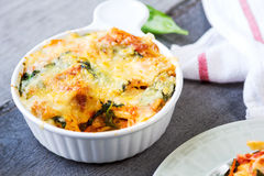 Baked pasta with spinach in tomato sauce Stock Images