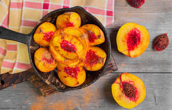 Baked peaches on a cast iron pan Stock Image