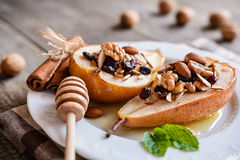 Baked pears with honey, walnuts, almond cranberries and cinnamon Royalty Free Stock Photo