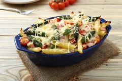 Baked penne rigate with tomatoes, asparagus, ham and cheese Stock Photos