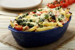 Baked penne rigate with tomatoes, asparagus, ham and cheese Stock Photography