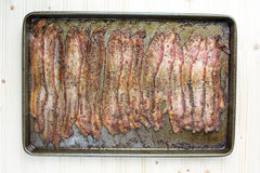 Baked Peppercorn Bacon in in baking pan on wood background Stock Photos