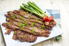 Baked Peppercorn Bacon in square white ceramic plate Stock Images
