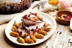 Baked pheasant. With bacon, pear, raisins on brandy Stock Photos