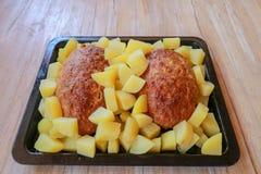 Baked picó el cerdo y las patatas en una bandeja del horno negra Comida puesta en la tabla de madera Fondo con las almohadas Almu fotos de archivo