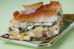 Baked pie with ham, spinach and boiled eggs. On plate Stock Photo