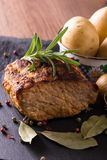Baked piece of pork meat on slate stone. Vertical photo of baked piece of pork meat with green rosemary herb on the top. Color pepper, bay leaf, onion, garlic Stock Photos