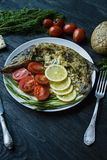 Baked pike in the oven, decorated with vegetables and herbs. Serving on a plate. Proper nutrition. Dark wood background stock photo
