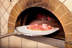 Baked pizza by the fire in oven Royalty Free Stock Photo