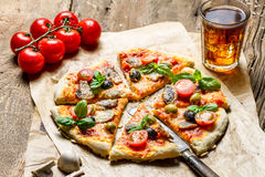 Baked pizza with fresh ingredients on old wooden table Stock Image