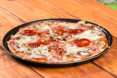 Baked pizza with mushrooms ham cheese on the round baking pan royalty free stock photos