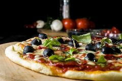Baked pizza with salami pepperoni, black olives, basil and mozarella cheese royalty free stock photography