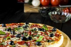 Baked pizza with salami pepperoni, black olives, basil and mozarella cheese stock images
