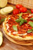 Baked pizza with tomatoes and zucchini. Delicious baked pizza with tomatoes sauce, basil and zucchini stock image