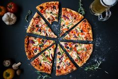 Baked Pizza on Top of Black Surface Near Filled Glass Tankard Royalty Free Stock Photo