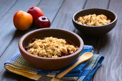 Baked Plum and Nectarine Crumble. Two rustic bowls filled with baked plum and nectarine crumble or crisp, photographed on dark wood with natural light (Selective Royalty Free Stock Photo