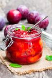 Baked  plums with  caramel and vanilla pod in a clear glass jar Royalty Free Stock Photo