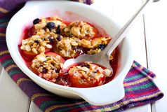 Baked plums with muesli crumble topping Stock Photo