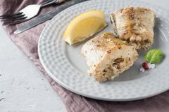 Baked Pollock fish with lemon and spices on a plate Napkin on the table.  stock photos