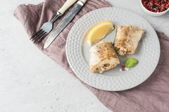 Baked Pollock fish with lemon and spices on a plate Napkin on the table.  royalty free stock image