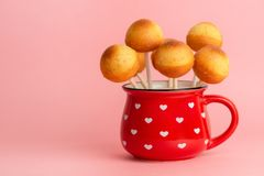 Baked pop cakes in cup ready for icing over pink background, hom Stock Photo